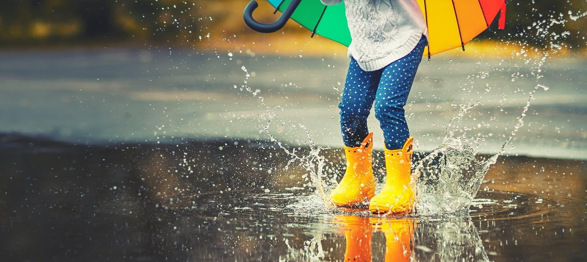 Child wearing rain boots jumping in a puddle with an umbrella